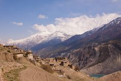 Scenic view of small nepali village with ancient buddhist stupa in the middle, rise fields, highland lake and huge cloudy peak cov royalty free stock photos