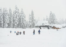 Scenic view of small people around ski resort when snowy day. Stock Images