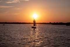 Scenic view of a small sailboat at a sunset in a city harbor. stock image