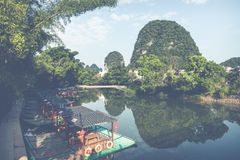 Scenic view of small tourist bamboo rafts sailing along the Yulo. Ng River among green woods and karst mountains at Yangshuo County of Guilin, China. Yangshuo is Royalty Free Stock Photo