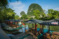 Scenic view of small tourist bamboo rafts sailing along the Yulo. Ng River among green woods and karst mountains at Yangshuo County of Guilin, China. Yangshuo is Stock Image