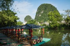 Scenic view of small tourist bamboo rafts sailing along the Yulo. Ng River among green woods and karst mountains at Yangshuo County of Guilin, China. Yangshuo is Royalty Free Stock Photos