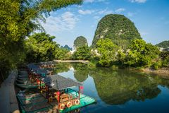 Scenic view of small tourist bamboo rafts sailing along the Yulo. Ng River among green woods and karst mountains at Yangshuo County of Guilin, China. Yangshuo is Stock Photos