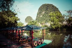 Scenic view of small tourist bamboo rafts sailing along the Yulo. Ng River among green woods and karst mountains at Yangshuo County of Guilin, China. Yangshuo is Stock Photo