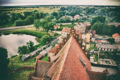 Scenic view of a small town, a pond and a tile church roof, old photo stylization Royalty Free Stock Photo