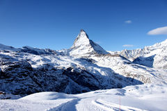 Scenic view on snowy Matterhorn peak in sunny day with blue sky and some clouds in background Royalty Free Stock Photography