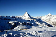Scenic view on snowy Matterhorn peak in sunny day with blue sky and some clouds in background Royalty Free Stock Image