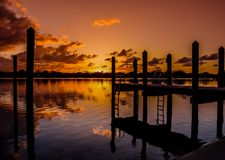 Ladders Up and Down in the Dawn. Scenic view of the sun rising over a lagoon in Florida as a dock`s ladders and pilings reflect in the rippled water stock photo