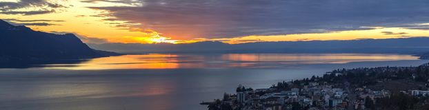 Scenic view of sunset over the Leman lake with yellow sky with clouds and Alps mountains in background, Montreux, Switzerland. Royalty Free Stock Images