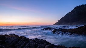 Scenic view of a sunset over ocean. Crushing waves enter into a chasm at Cape Perpetual, Oregon Coast royalty free stock photo