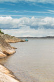 Scenic view of swedish coast. Scenic view of a beach in sweden. A small boat is anchored a bit further out in the water stock image