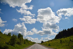Scenic view to the road in mountains with beautiful sky. Scenic view to the road in mountains with blue sky and huge clouds Stock Photography