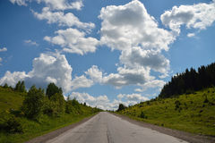 Scenic view to the road in mountains with beautiful sky. Scenic view to the road in mountains with blue sky and huge clouds Royalty Free Stock Photo