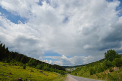 Scenic view to the road in mountains with beautiful sky. Scenic view to the road in mountains with blue sky and huge clouds Stock Photo