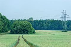 Scenic view tractor tracks in plantation of cereal plants and high voltage towers, electricity pylons in the distant. Germany royalty free stock photo