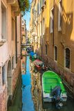 Narrow canal with colorful boats in Venice, Italy. Scenic view of Venice narrow canal with old architecture and colorful boats Royalty Free Stock Photos