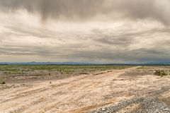 Scenic view on very long road till horizon. Boundless Kazakh steppes. Dramatic sky and clouds. Mountains afar Royalty Free Stock Image