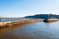 Scenic view of Whitby Lighthouse and Pier in sunny autumn day, UK Royalty Free Stock Images