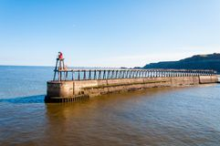 Scenic view of Whitby Lighthouse and Pier in sunny autumn day, UK Royalty Free Stock Photography