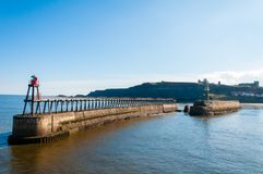 Scenic view of Whitby Pier in sunny autumn day.Whitby is a seaside town and port in North Yorkshire, UK. Its attraction as a touri Stock Photography