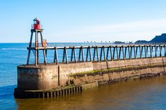 Scenic view of Whitby Pier in sunny autumn day.Whitby is a seaside town and port in North Yorkshire, UK. Its attraction as a touri Royalty Free Stock Image