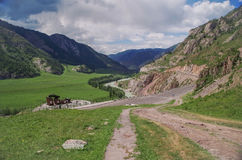 Scenic view of the winding mountain river, empty trunk road, green fields, valley and mountains. Royalty Free Stock Image