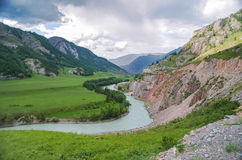 Scenic view of the winding mountain river, green fields, valley and mountains. Stock Photos