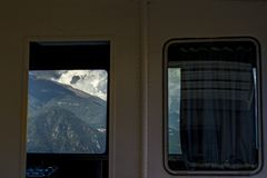 Scenic view of the yacht cabin window on the mountains in Italy on Lake Como. Scenic view of the yacht cabin window on the mountains and sky in Italy on Lake stock photo
