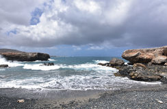 Scenic Views of Aruba`s Black Sand Stone Beach. Pretty view of Aruba`s black sand stone beach with waves lapping the shore Stock Images