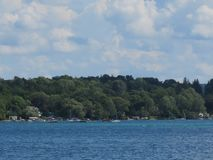 Brilliant blue sky, fluffy white clouds and a lake. Scenic views of Skaneateles Lake in New York State, with a lovely bright blue sky and blue water. Could make royalty free stock photography