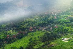 Scenic Vista View of Peaceful Countryside Village with Lush Green Rice Terrace Field on Mountain. Slope in Morning Fog During Sunrise stock images