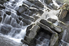 Scenic waterfall. With water flowing over rocks Stock Images