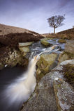 Scenic waterfall in moorland. Scenic view of picturesque waterfall in moorland landscape with slow motion and lone tree in background, Pennines, Haworth, West Royalty Free Stock Photography