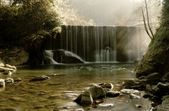 Scenic waterfall stream in silky effect. A scenic waterfall stream in silky effect, sun light beams from comming from the left Stock Image