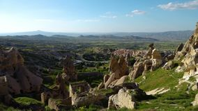 Scenic cone-shaped rock formations and caves of Cappadocia. A scenic wide shot of Cappadocia cone-shaped rock formations and man-made cave structures stock video footage