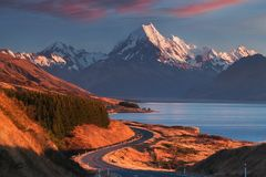 Scenic winding road along Lake Pukaki to Mount Cook National Park, South Island, New Zealand during cold and windy autumn morning. royalty free stock photography