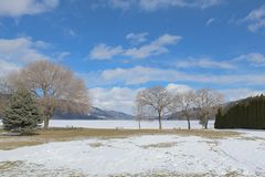 Scenic winter field and lake landscape stock photos