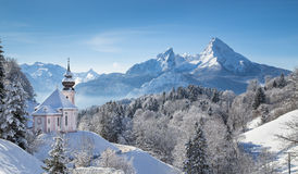 Scenic winter landscape in the Alps with church. Panoramic view of beautiful winter landscape in the Bavarian Alps with pilgrimage church of Maria Gern and Royalty Free Stock Images