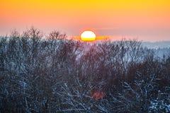 Scenic winter landscape at sundown. Scenic winter landscape of orange sundown in forest royalty free stock photography