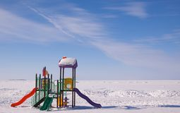 Scenic winter view of colored playground on deserted beach covered with snow. royalty free stock photo