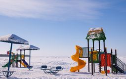 Scenic winter view of sun umbrellas, swing and colorful playground on deserted beach covered with snow. Blue sky with cirrus clouds and frozen sea background Royalty Free Stock Photos