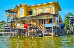 The scenic wooden house on Inle Lake, Myanmar. The scenic colorful wooden two-story house on stilts on Inle Lake, Inpawkhon, Myanmar stock image