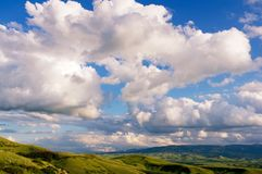 Scenic Wyoming near the Big Horn Mountains. Big puffy clouds over green hills near the Big Horn Mountains in Wyoming Royalty Free Stock Images