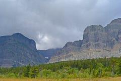 Scenico dei campi, degli alberi e delle montagne massicce profila il Glacier National Park immagini stock