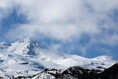 Sceniczna śnieżna góra stronniczo zakrywająca mgłami z niebieskim niebem w tle zdjęcie stock
