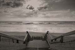 Sceniczna biscarrosse plaża w zmierzchu z chmurami i drewnianymi footpath schodkami w czarny i biały sepiowym, France Zdjęcie Stock
