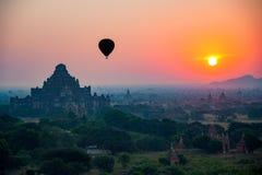 Sceniczna piękna słońce wzrosta gorącego powietrza balonu komarnica nad antycznym pagody polem Zdjęcie Stock
