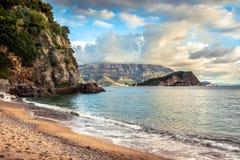 Sceniczna plaża z falezą i skały otaczać z wibrującą przejrzystą turkus wodą podczas zmierzchu w Europa kraju na Montenegr Obrazy Stock