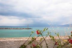 Sceniczny Egejski seascape z kwiatami i latarnią morską Zdjęcia Royalty Free