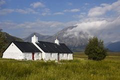 Sceniczny Glencoe z uroczym bielu domem - Croft w szkockich średniogórzach, Szkocja zdjęcia stock
